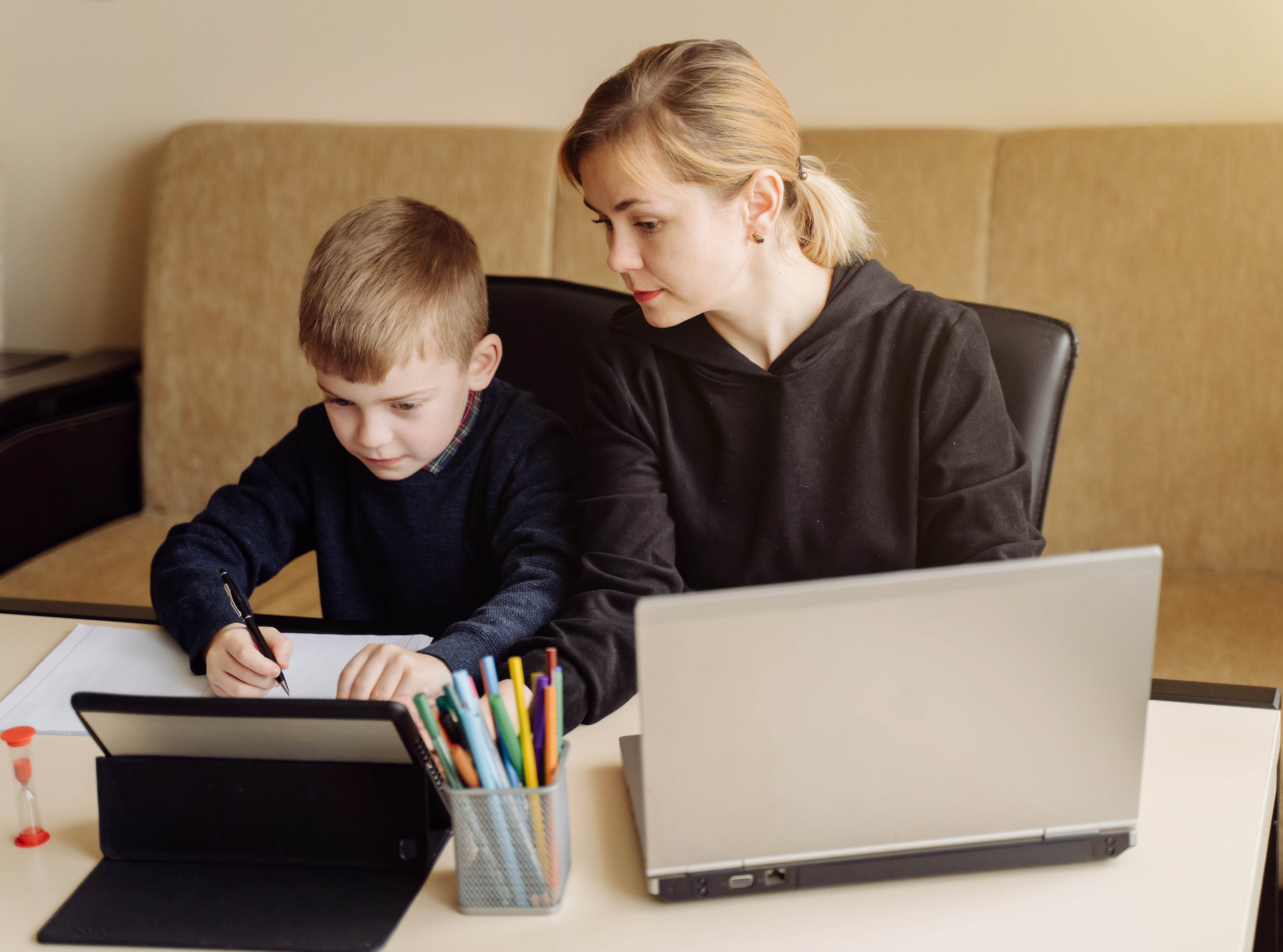 Mother using laptop and tablet teaching with her son online at home in his room